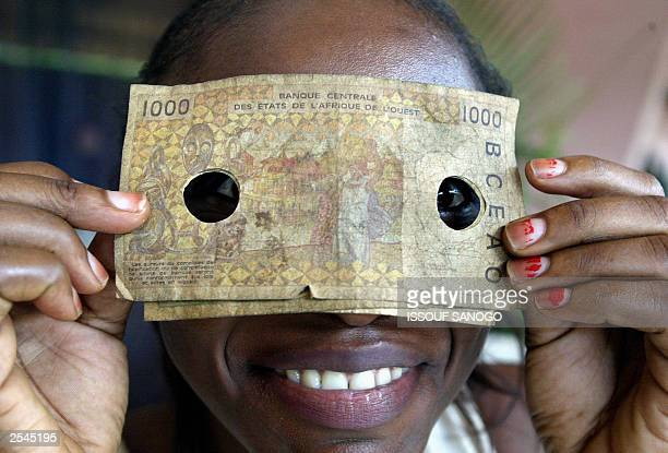 A young local girl hides her face with a punched banknote in Bouake 29 September 2003 Most of the banknotes were issued by a branch of the West...