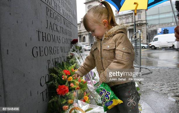 A young local girl looks at the flowers placed on the memorial on Talbot Street in Dublin to the victims of the Dublin and Monaghan bombings in 1974...