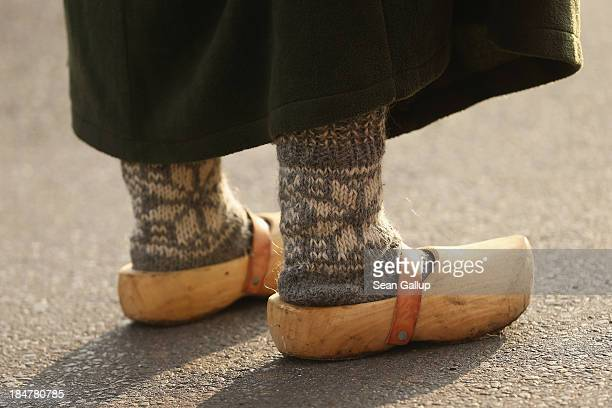 A young local woman dressed in early19th century regional period clothing and wearing wooden clogs walks through a recreated 1813 village in...