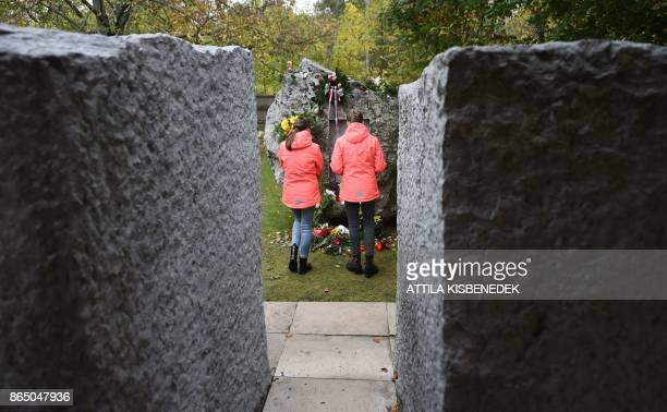 Young locals stand in front of the memorial stone at the Koztemeto cemetery for the victims of the 1956 uprising against Soviet occupation in...