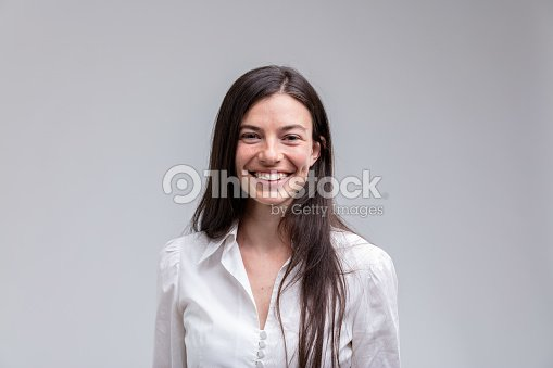 Young long-haired smiling woman in white shirt : Stock Photo
