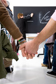 Two students hold hands in class.