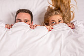 Young lovely couple lying in a bed, looking at camera, cover under blanket top angle view up above