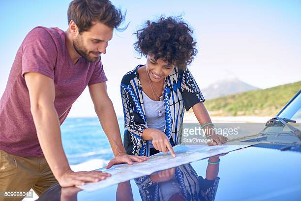 Young lovely couple using  map during roadtrip