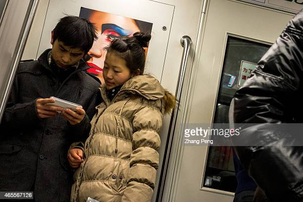 Young lovers watch videos on their smart phones in the subway People who have the smartphoneaddict nowadays are called Smartphone zombies