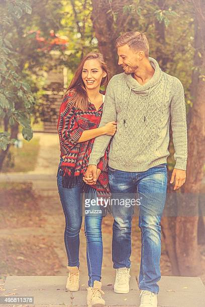 Young loving couple holding hands in stroll through the nature