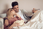Happy young couple relaxing and watching TV at home