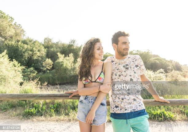 Young loving couple looking away outdoors in Tuscany