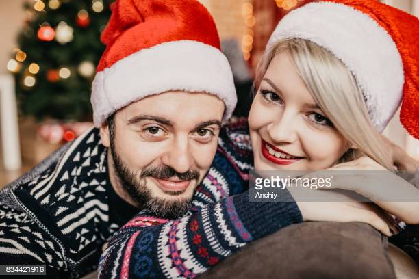 Young loving couple making selfie with Christmas Tree in the background