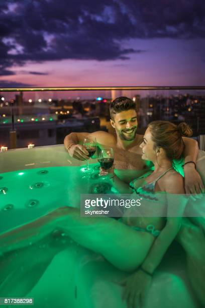 Young loving couple toasting with wine in a hot tub.