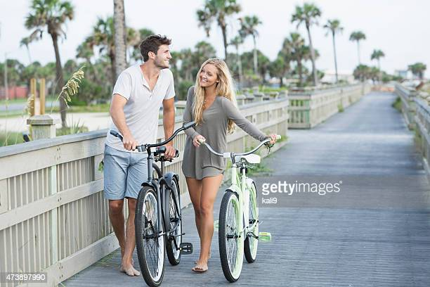 Young loving couple walking with their bicycles