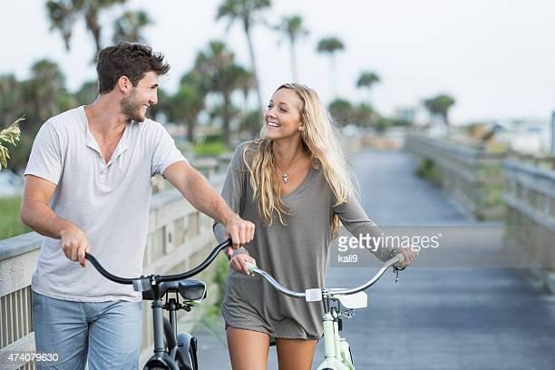 Junge Liebende paar walking mit ihre Fahrräder