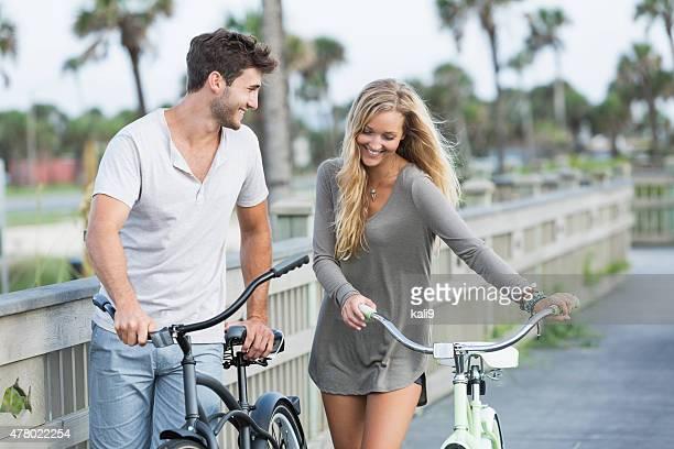 Giovane Coppia di innamorati a camminare con le loro biciclette