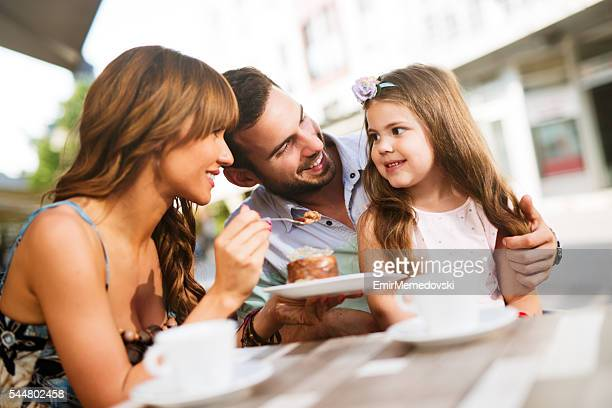 Young loving family having fun in a cafe eating cake.