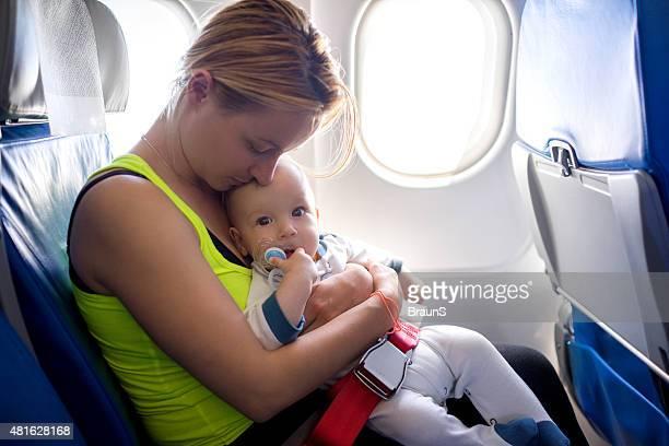 Amante joven madre con su bebé que viajan en avión.