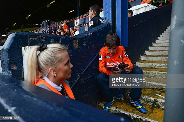 A young Luton fan reads his programme on the steps at the foot of a floodlight pylon watched by a steward during the Skrill Conference Premier match...