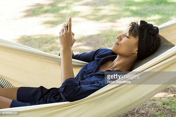Young lying Woman in hammock with mobile phone