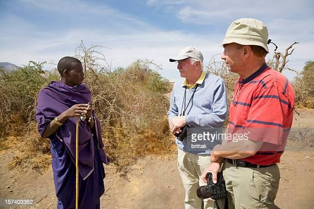Young Maasai man in traditional shuka with European tourists. Tanzania
