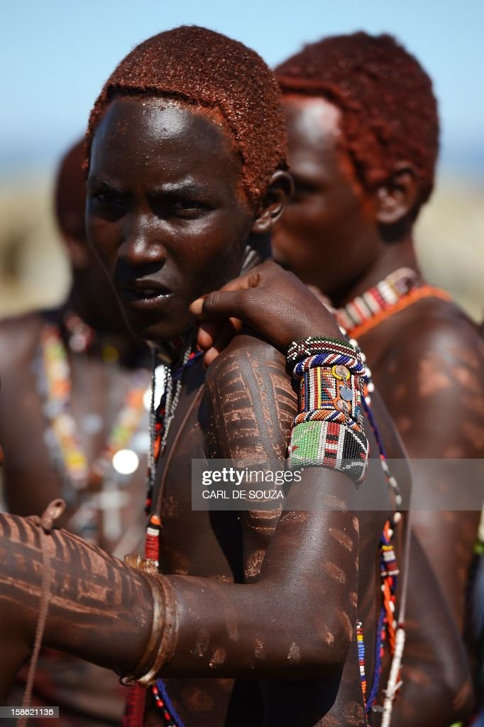A young Maasai warrior or 'Moran' looks on as he celebrates with others by dancing, as they arrive at Mount Suswa in Kenya on December 20, 2012. Mount Suswa is a sacred place for the Maasai tribe and every 10 years Maasai from all over Kenya gather to witness the coming of age ceremony for the Morans known as an 'Age Set'. The 'age set' sees Morans achieving the status of manhood in their communities' eyes. Before this coming of age ceremony Morans must traditionally be circumcised and spend up to 4 years in the wilderness with a group of around 10 or less to fend for themselves and put into practice hunting techniques and life skills passed on by their elders. AFP PHOTO / Carl de Souza