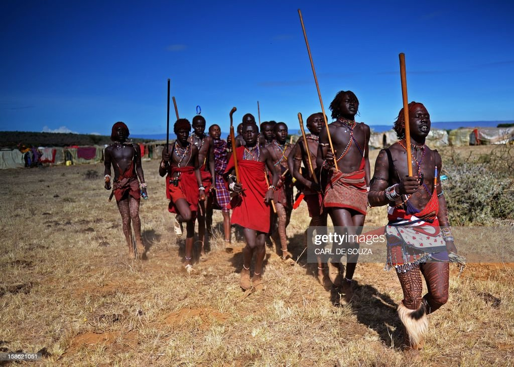 Young Maasai warriors or 'Morans' celebrate by dancing as they arrive at Mount Suswa in Kenya on December 20, 2012. Mount Suswa is a sacred place for the Maasai tribe and every 10 years Maasai from all over Kenya gather to witness the coming of age ceremony for the Morans known as an 'Age Set'. The 'age set' sees Morans achieving the status of manhood in their communities' eyes. Before this coming of age ceremony Morans must traditionally be circumcised and spend up to 4 years in the wilderness with a group of around 10 or less to fend for themselves and put into practice hunting techniques and life skills passed on by their elders. AFP PHOTO / Carl de Souza