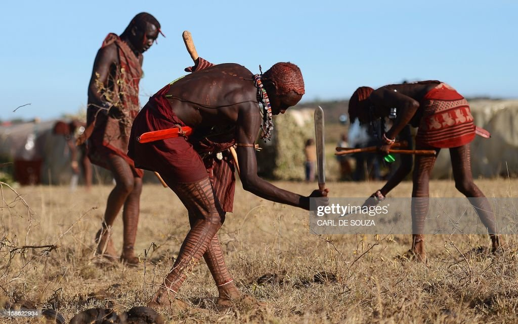 Young Maasai warriors or 'Morans' clear the ground with machetes at Mount Suswa in Kenya on December 20, 2012. Mount Suswa is a sacred place for the Maasai tribe and every 10 years Maasai from all over Kenya gather to witness the coming of age ceremony for the Morans known as an 'Age Set'. The 'age set' sees Morans achieving the status of manhood in their communities' eyes. Before this coming of age ceremony Morans must traditionally be circumcised and spend up to 4 years in the wilderness with a group of around 10 or less to fend for themselves and put into practice hunting techniques and life skills passed on by their elders. AFP PHOTO / Carl de Souza
