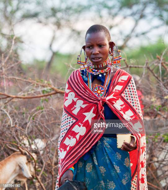 Young Maasai woman has milked goat milk into mug