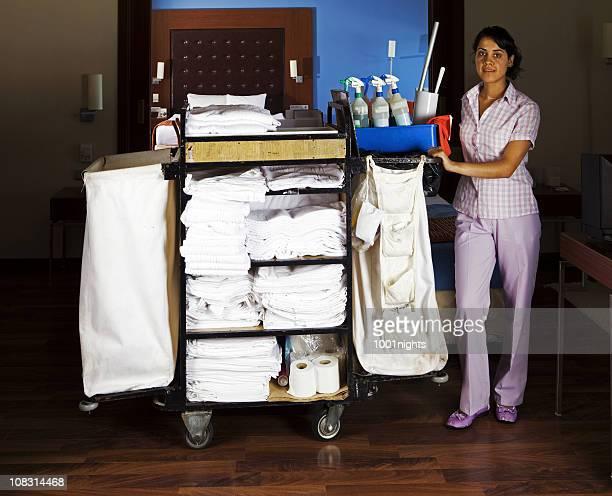Giovane cameriera pulizia della suite di hotel