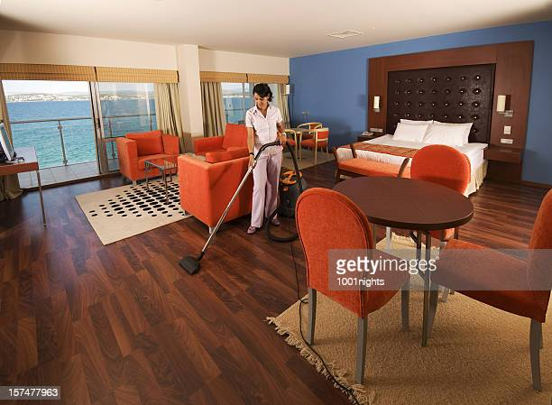 Young maid cleaning the hotel suite
