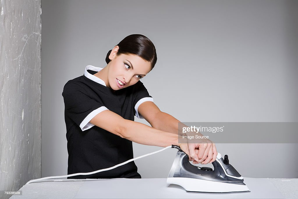 Young maid ironing : Stock Photo