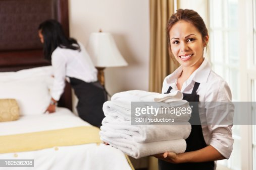 Young maids cleaning and preparing room for hotel guests