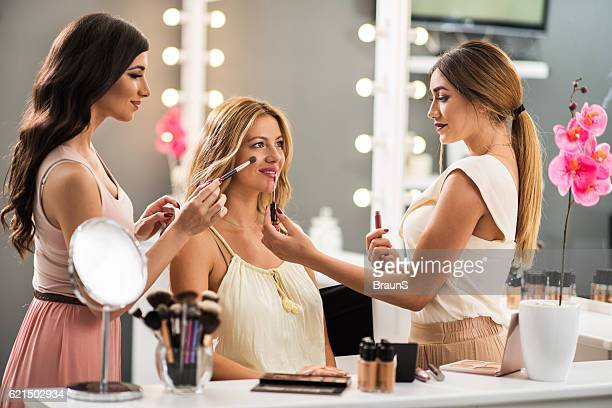 Young make-up artists working on beautiful woman in beauty salon.