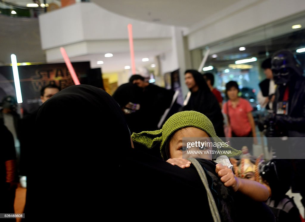 A young Malaysian dressed as baby Yoda clings on to her mother during an event to mark the Star Wars Day celebration in Kuala Lumpur on April 30, 2016. / AFP / MANAN