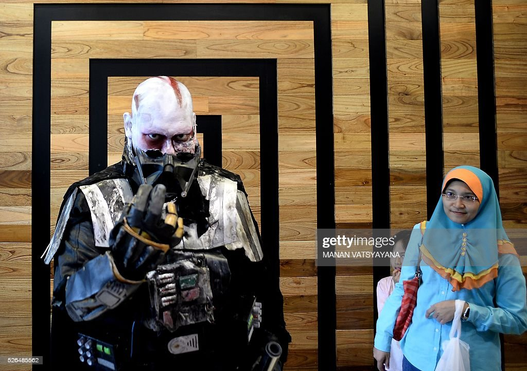 A young Malaysian girl (C) hides behind her mother as Khalil Ishak dressed as Darth Vader (L) poses during an event to mark the Star Wars Day celebration in Kuala Lumpur on April 30, 2016.
