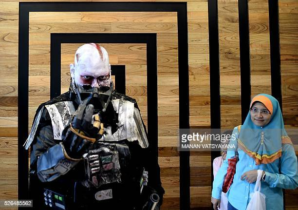 A young Malaysian girl hides behind her mother as Khalil Ishak dressed as Darth Vader poses during an event to mark the Star Wars Day celebration in...
