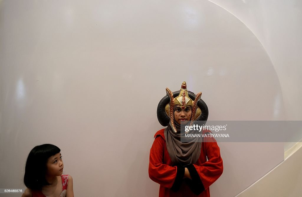 A young Malaysian girl (L) watches as Hanani Wan (R) dressed as popular 'Star Wars 'character Queen Padm�� Amidala poses during an event to mark the Star Wars Day celebration in Kuala Lumpur on April 30, 2016. / AFP / MANAN