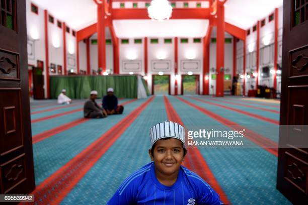 A young Malaysian Muslim boy sits in the courtyard before breaking his fast during the holy month of Ramadan at the MelakaChinese mosque in Krubong...