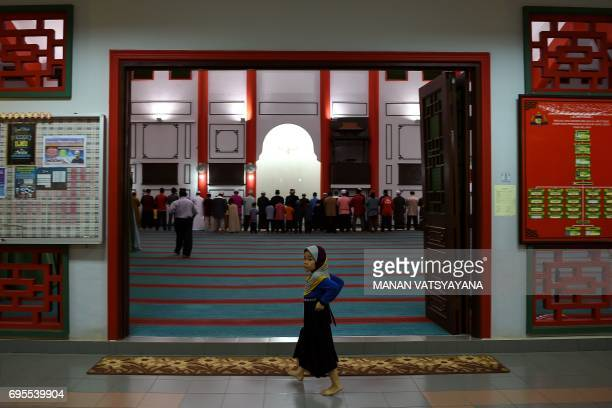 A young Malaysian Muslim girl walks past as others offer evening prayers during the holy month of Ramadan at the MelakaChinese mosque in Krubong...