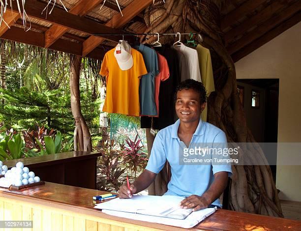 Young Maldivian working at resort golf shop