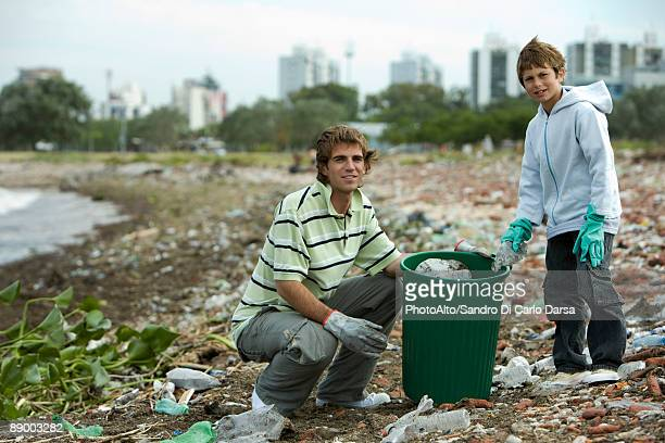 Young male and boy picking up trash on polluted shore