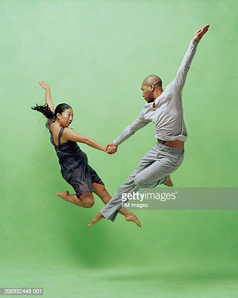 Young male and female dancers leaping