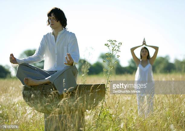 Young male and female doing yoga in field