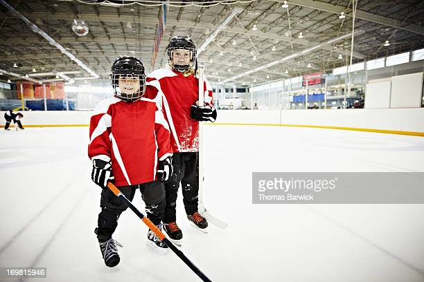 Young male and female ice hockey players on ice