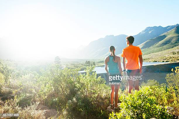 Young Male and Female Runner Look Over Nature Reserve