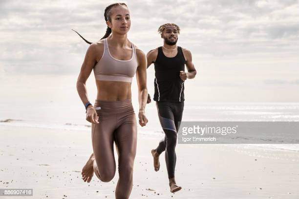 Young male and female runners running barefoot along beach