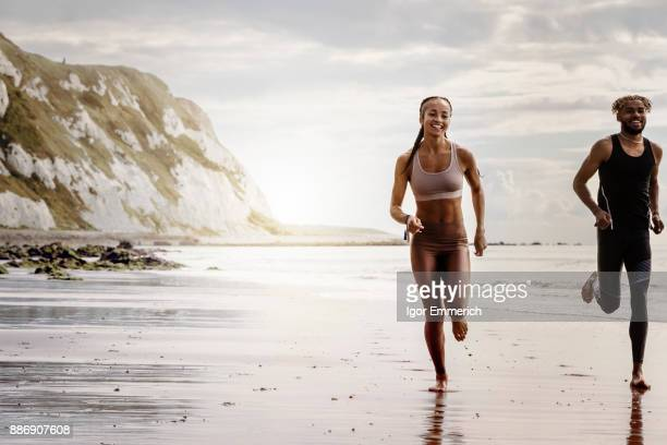 Young male and female runners running barefoot on beach