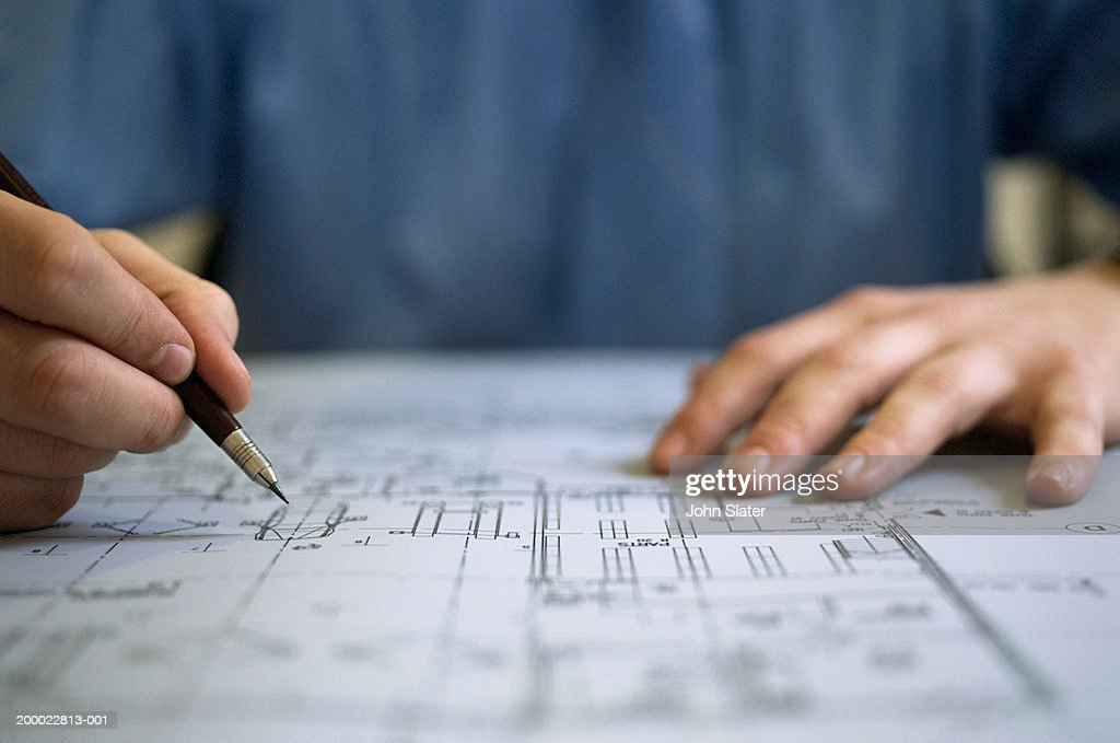 Young male architect working on plans, close-up