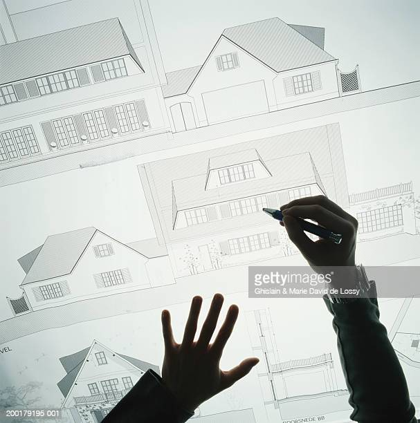 Young male architect working on plans, elevated view, close-up