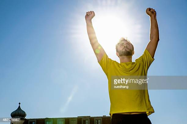 Young male athlete celebrating on city rooftop