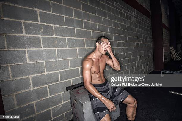 Young male athlete sitting having a break in gym