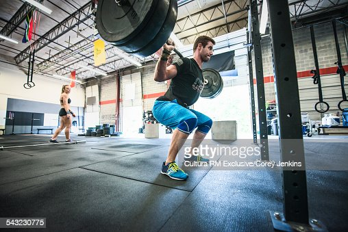 Young male athlete squatting to lift bar bell on shoulders in gym